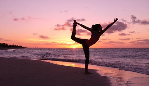 girl performing yoga on the beach